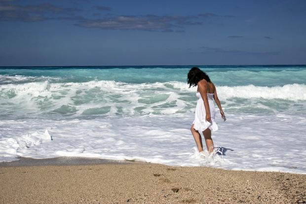 девушка в белом сарафане идет по морю