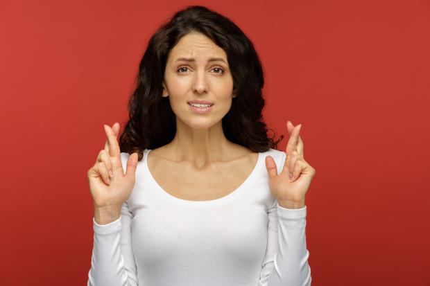 темноволосая девушка в белом реглане скрестила пальцы