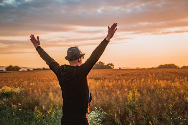Мужчина стоит в поле раскинув руки