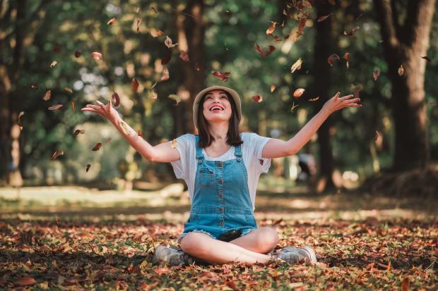 Девушка в джинсовом комбинезоне бросает листья