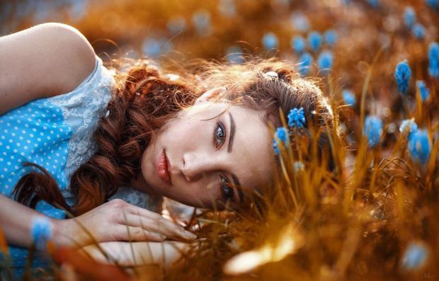 женщина в голубом платье лежит на земле рядом с голубыми цветами