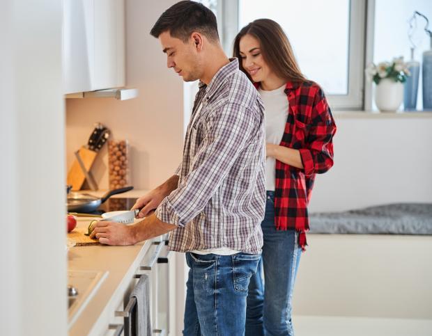 молодой мужчина и девушка готовят еду на кухне