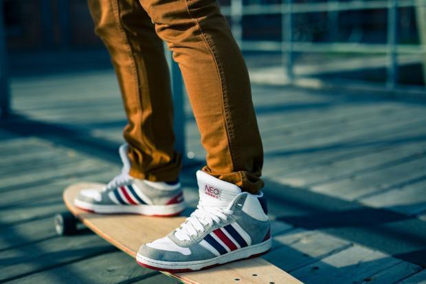 человек стоит на скейтборде в кроссовках