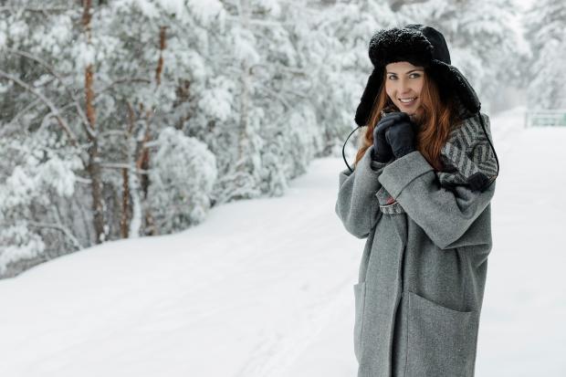 в зимнем лесу стоит девушка в пальто и шапке-ушанке