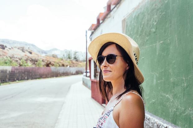 стоит девушка в шляпе и солнцезащитных очках