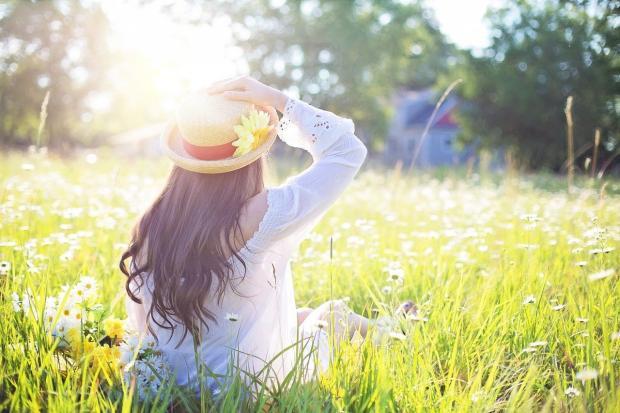 девушка в белой рубашке и шляпке сидит на цветущем лугу