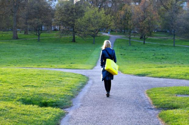 девушка с желтой сумкой подходит к развилке дорог