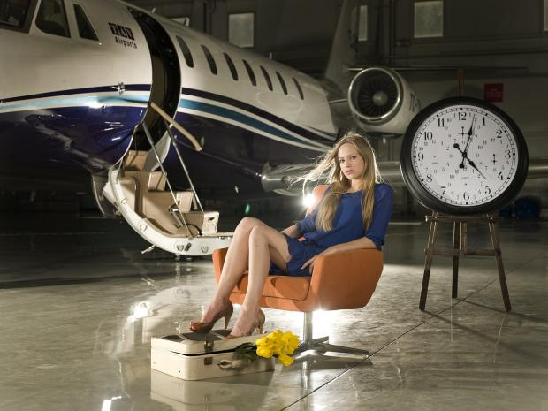 девушка сидит в кресле рядом с самолетом и большими часами