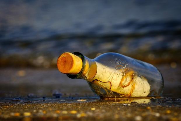 стеклянная бутылка с запечатанным посланием лежит на берегу моря