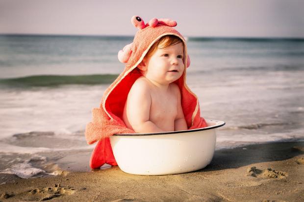 малыш в тазике с полотенцем на голове на берегу моря