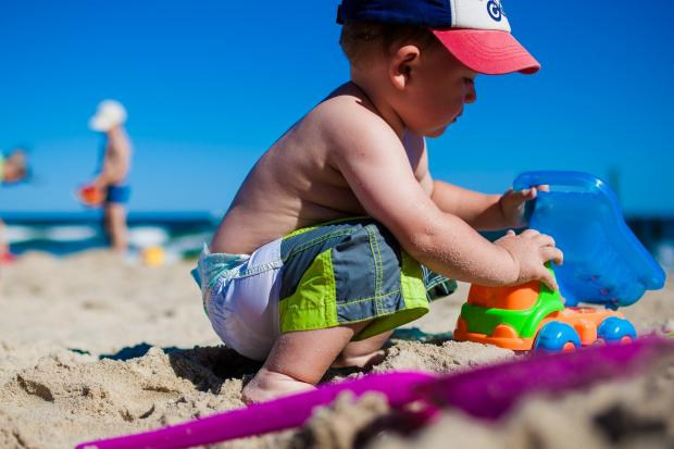 мальчик играет на берегу в песке с игрушками