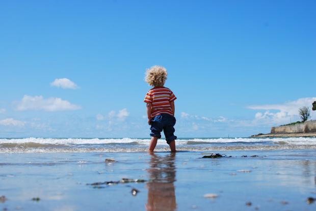 мальчик стоит в воде на берегу моря