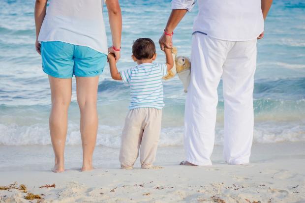 родители держат малыша за руки на берегу моря