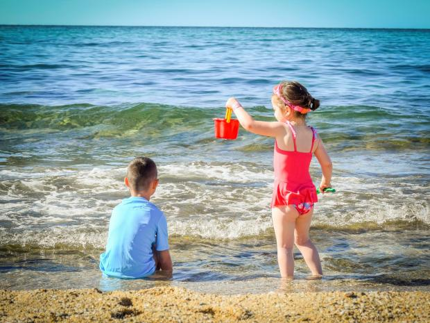 девочка и мальчик играют на берегу моря