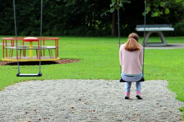 девушка качается на качелях на детской площадке