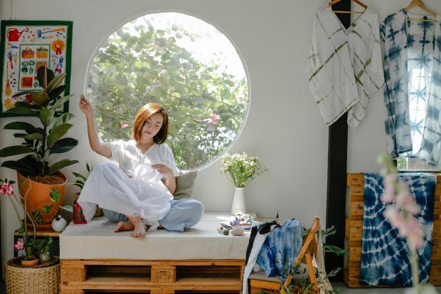 девушка в белом платье сидит возле круглого окна