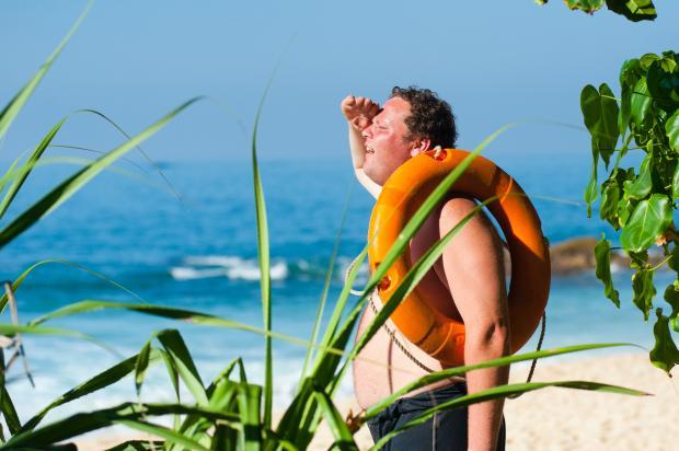 мужчина с надувным кругом на пляже