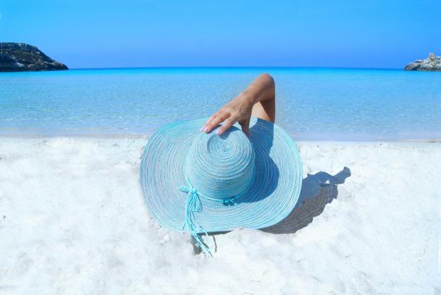 синяя шляпка и женская рука на пляже
