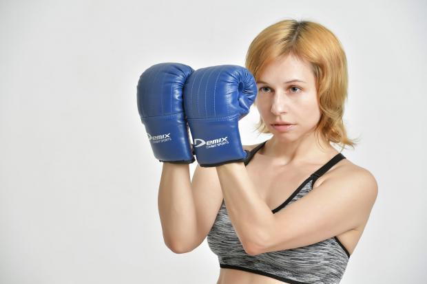 стоит девушка в синих боксерских перчатках
