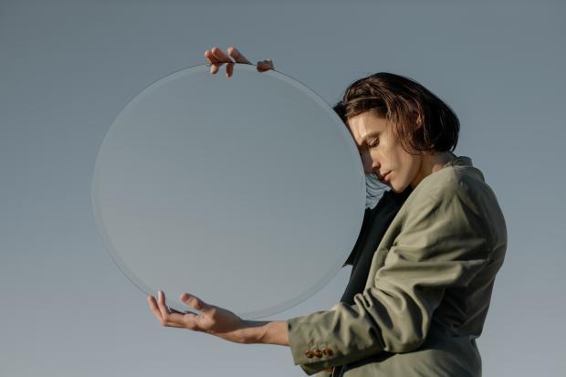 женщина держит круглое зеркало в руках