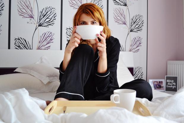 девушка в пижаме на кровати держит в руках мисочку с завтраком
