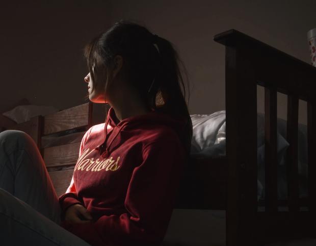 девушка в красном худи сидит возле кровати