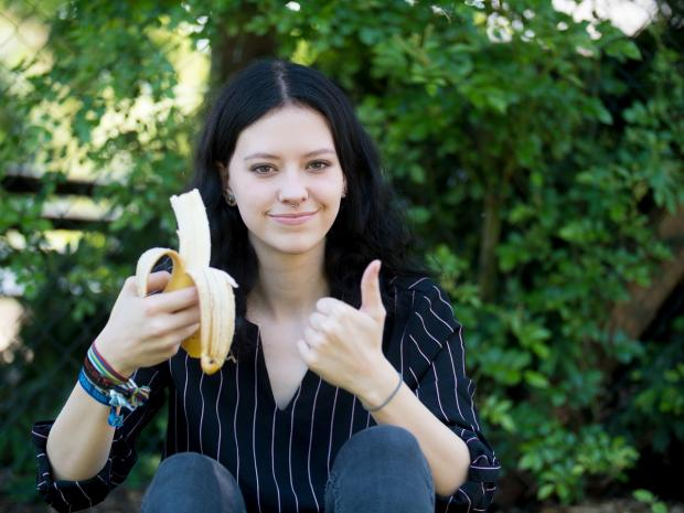 брюнетка с бананом показывает большой палец вверх