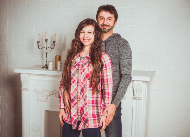 счастливая пара стоит на фоне белого камина