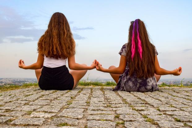 две девушки медитируют на природе