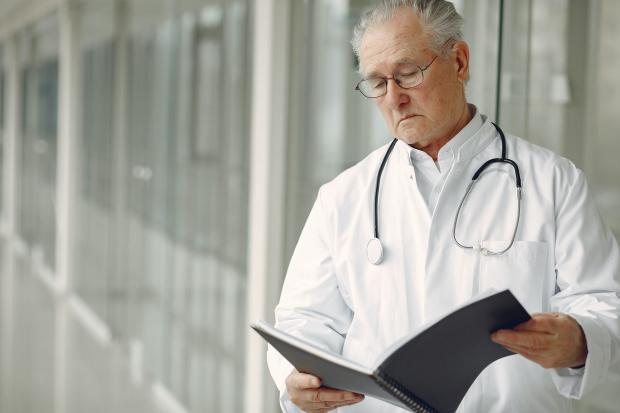 мужчина-врач в белом халате с черной папкой в руках