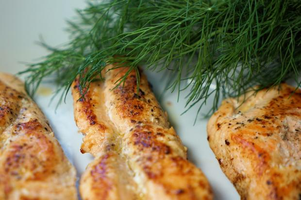 на тарелке лежит запеченный лосось с укропом