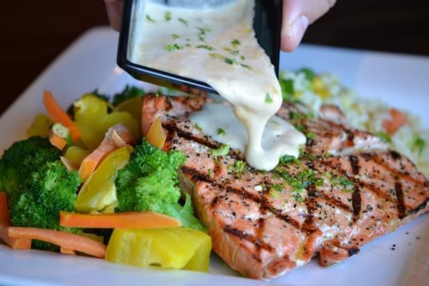 на запеченный лосось льют белый соус