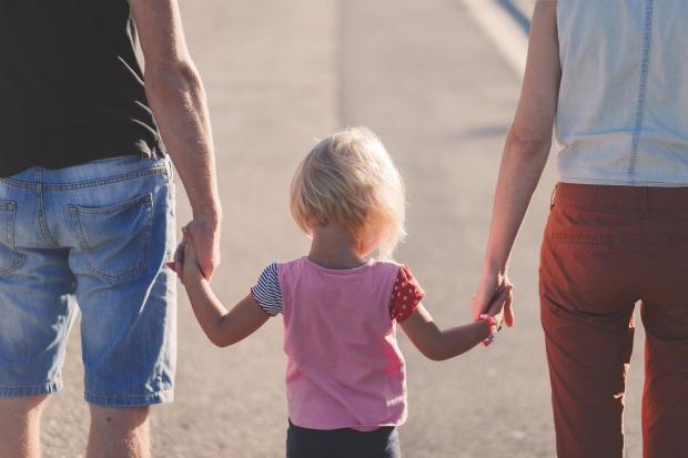 родители ведут за руки маленькую дочь
