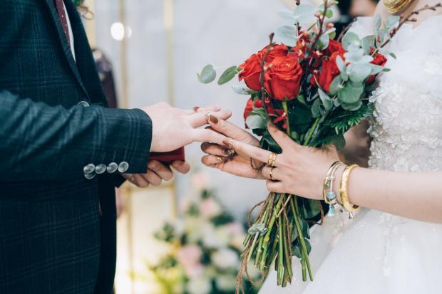 невеста с букетом в руке надевает обручальное кольцо жениху