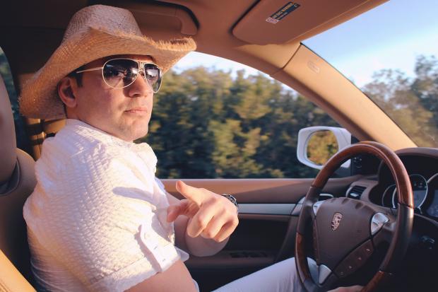 мужчина в белой рубашке и ковбойской шляпе за рулем