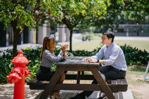 мужчина и девушка разговаривают за столом на улице