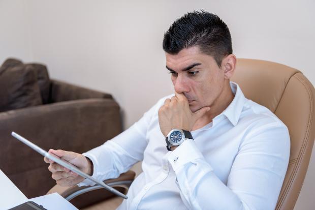 мужчина в кресле смотрит планшет