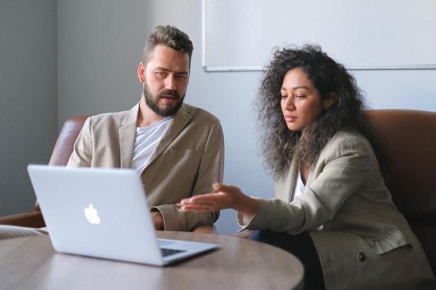 мужчина и женщина за столом обсуждают, глядя в ноутбук
