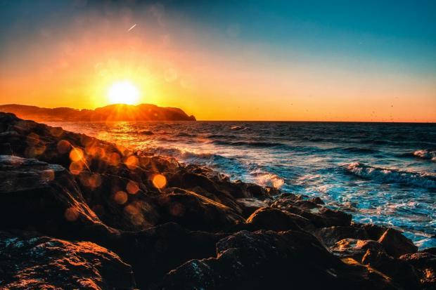 восход Солнца над морским побережьем