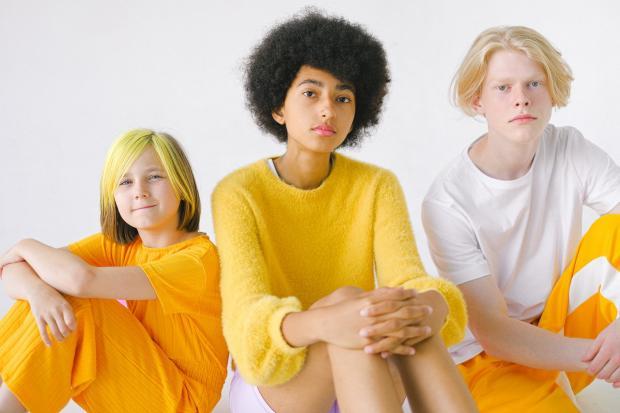 сидят трое друзей в желтой одежде и с разными прическами