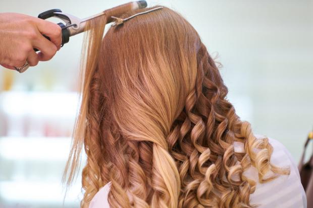 парикмахер завивает волосы