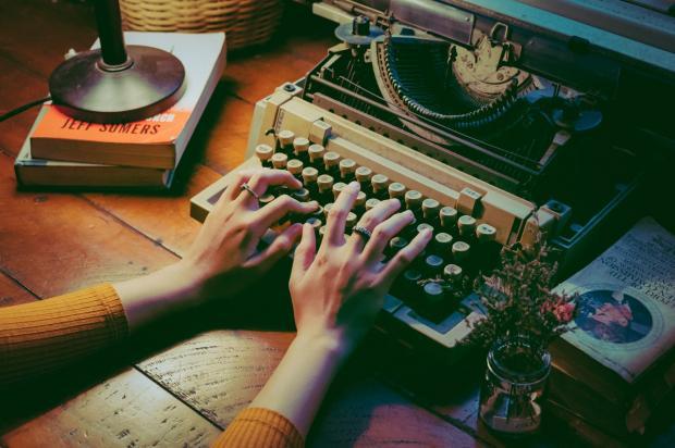 девушка печатает на механической пишущей машинке