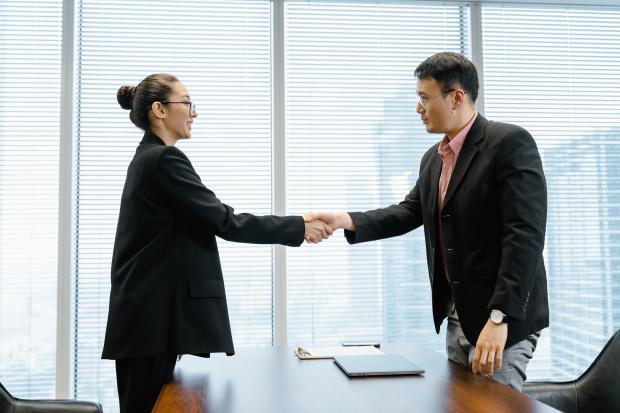 мужчина и женщина в деловых костюмах жмут друг другу руки