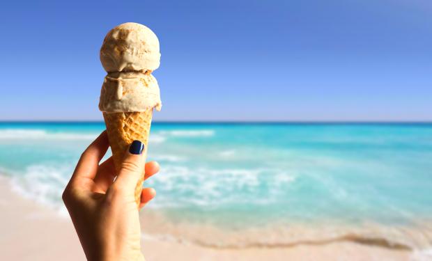 мороженое в женской руке на фоне пляжа и моря