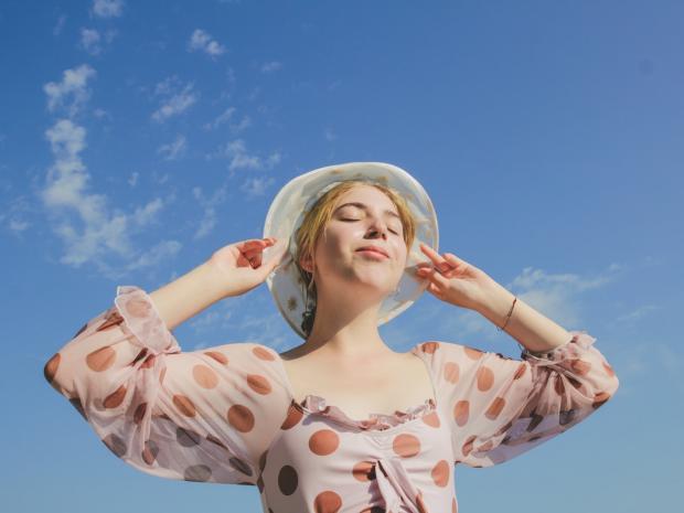 девушка в летнем платье и шляпке стоит под голубым небом