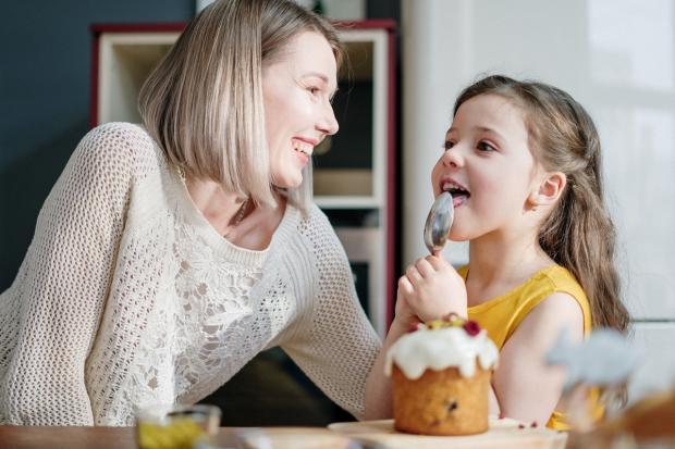 женщина готовит кулич на кухне с ребенком