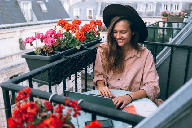 женщина в шляпе сидит на балконе среди цветов
