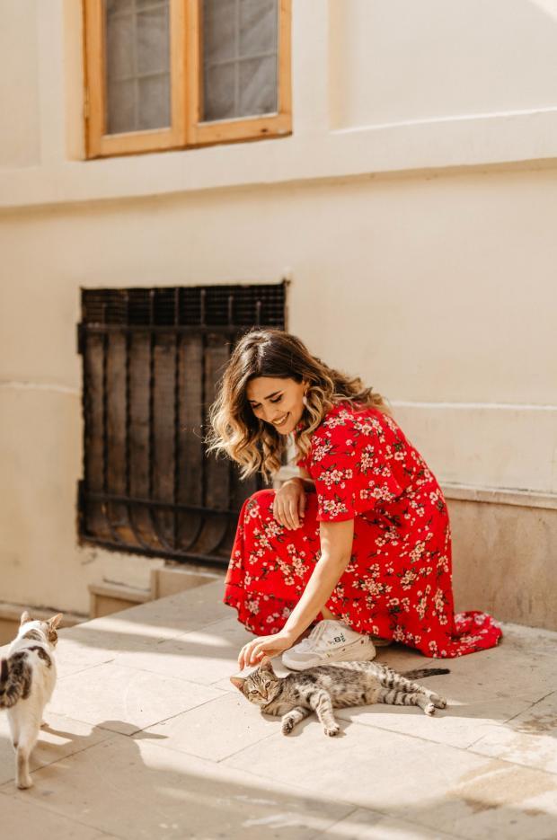 длинноволосая девушка в красном платье гладит котенка