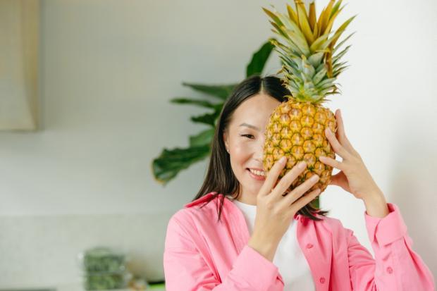 брюнетка в розовой рубашке спрятала лицо за ананасом