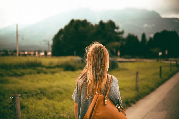 девушка с коричневой сумкой на плече идет по дороге